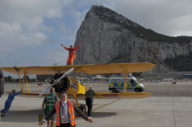 British daredevil Tom Lackey, 94, waves to the crowd before he wing-walks on a bi-plane flying around the Rock (rear) of the British Colony of Gibraltar, October 11, 2014. Lackey, who currently holds several Guinness World Records, achieved one of his remaining ambitions, flying strapped to the top wing of a vintage Boeing Stearman bi-plane. (Photo by Jon Nazca/Reuters)