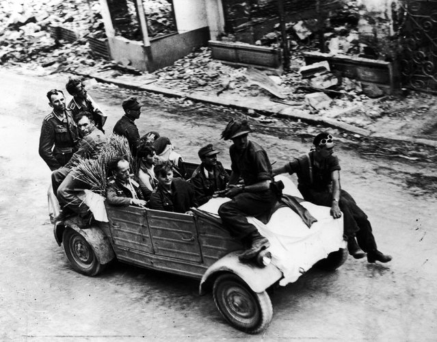 German troops drive into the French town of Trun under a white flag of surrender, 1944. (Photo by Keystone)