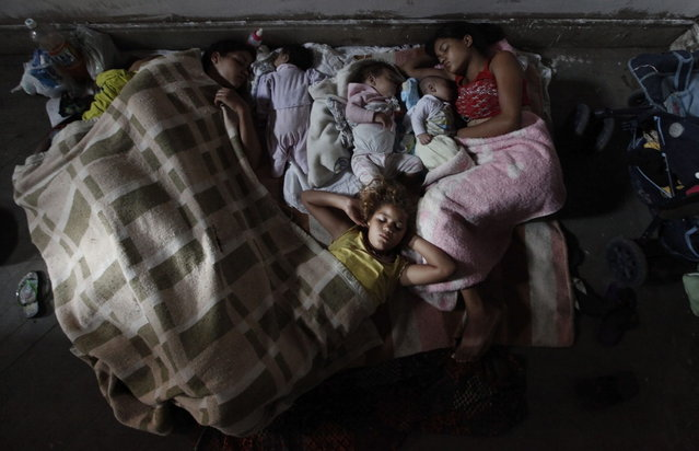 Members of Brazil's Movimento dos Sem-Teto (Roofless Movement) sleep on the floor of a vacant apartment in one of the 11 empty buildings that the movement took over in one night, in the centre of Sao Paulo, October 29, 2012. According to City Hall, there are some 400,000 people in need of stable housing, including the 4,000 families of the Roofless Movement who are squatting in abandoned or vacant buildings that range from apartment blocks to hotels, in Sao Paulo, the largest city in South America. (Photo by Nacho Doce/Reuters)