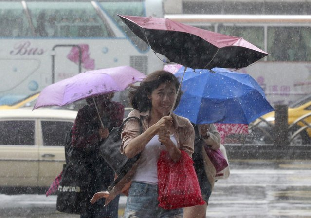 People hold their umbrellas while walking against strong winds caused by Typhoon Dujuan in Taipei, Taiwan, September 28, 2015. (Photo by Pichi Chuang/Reuters)