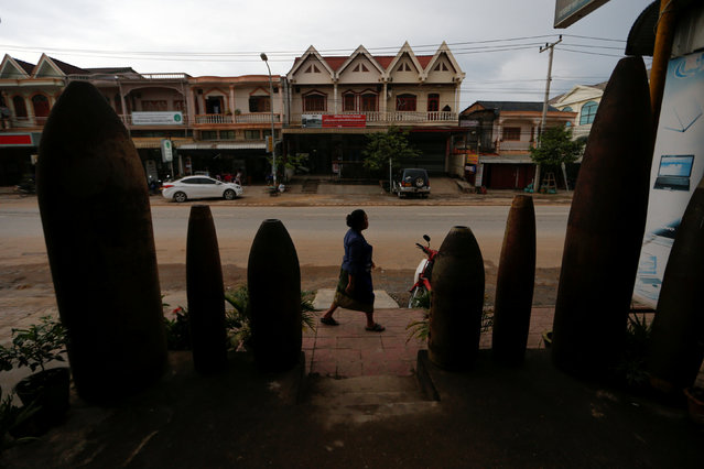 A woman walks past a restaurant decorated with unexploded bombs dropped by the U.S. Air Force planes during the Vietnam War, in Xieng Khouang, Laos September 2, 2016. (Photo by Jorge Silva/Reuters)