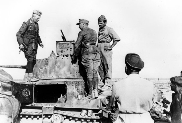 Commander-in-chief of the German Africa Corps. Gen. Erwin Rommel, left, holding binoculars, watches enemy movement from a tank in the foremost lines on the North African Front on June 30, 1941 during World War II.  Rommel is surrounded by German and Italian soldiers. (Photo by AP Photo)