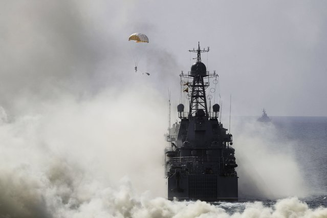 Russian navy ships and military paratroopers take a part in a landing operation during military drills at the Black Sea coast, Crimea, Friday, September 9, 2016. (Photo by Pavel Golovkin/AP Photo)