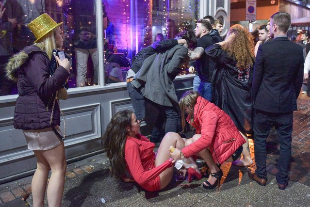 A girl is helped up by her pal in Birmingham, England on December 31, 2017 as lads trade blows behind her. (Photo by Caters News Agency)