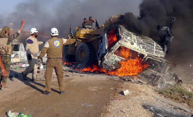 This photo provided by the Syria Press Center (SPC), an anti-government media group, shows rescue workers using a bulldozer to remove a burned van after airstrikes hit west of the town of Suran in Hama province, Syria, Thursday September 1, 2016, killing a dozen people. Suspected government warplanes carried out a series of airstrikes in Hama amid a lightning advance by insurgents on government-controlled areas in the province. (Photo by Syria Press Center via AP Photo)
