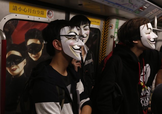 Pro-democracy protesters wearing Guy Fawkes masks stand in front of an advertisement as they take a subway train to a protest site occupied by them as part of the Occupy Central civil disobedience movement in Hong Kong November 5, 2014, the day marking Guy Fawkes Night. (Photo by Bobby Yip/Reuters)