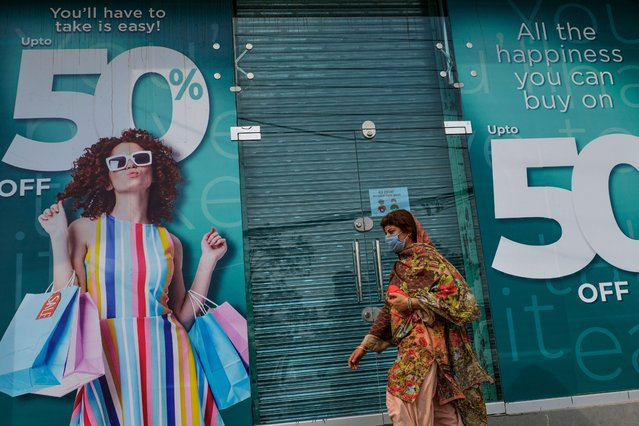 "A woman walks past a shuttered market in Rawalpindi on July 29, 2020, after the Punjab province government announced a lockdown closing markets, shopping malls and plazas to contain the spread of the COVID-19 coronavirus on the occasion of the Muslim festival Eid al-Adha or the ""Festival of Sacrifice"". (Photo by Farooq Naeem/AFP Photo)"