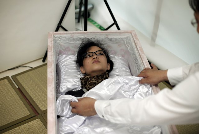 A staff member covers Natsumi Niki with a quilt as she lies in a coffin to test it during an end-of-life seminar held by Japan's largest retailer Aeon Co in Tokyo October 24, 2014. (Photo by Toru Hanai/Reuters)