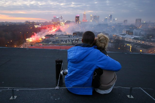A young couple sit on the roof of a building and watch the 'March of Independence' marking Polish Independence Day near the National Stadium in Warsaw, Poland, 11 November 2014. Poland's Independence Day, marks the restoration of Poland's independence at the end of the First World War on 11 November 1918, after 123 years of partitions by Austria-Hungary, Prussia, and Russia. (Photo by Pawel Supernak/EPA)
