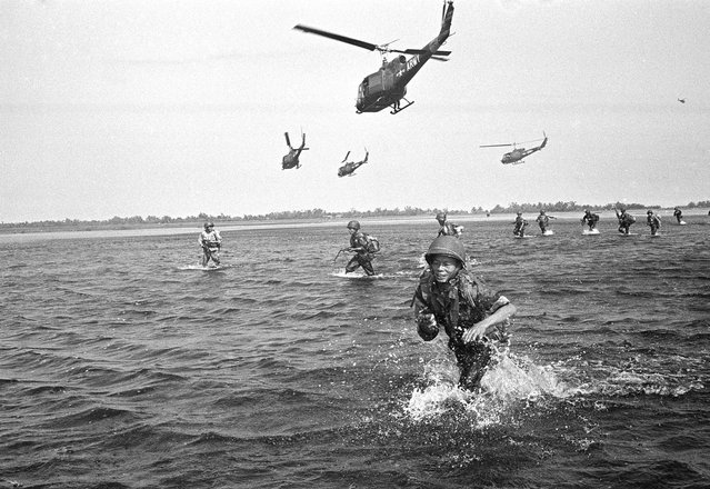 One trooper sprawls in the flooded swamp as other Vietnamese Government Soldiers walk through the water after landing from U.S. army Helicopters near CA Mau Peninsula in South Vietnam on September 15, 1963. The Soldiers were landed to pursue communist Viet Cong Guerrillas who had attacked a Vietnamese outpost. (Photo by Horst Faas/AP Photo)