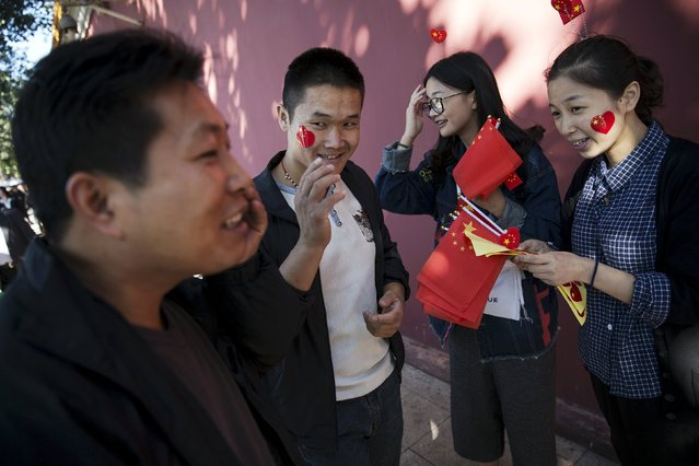 Young men place stickers in national colours on their faces after getting them from young women near Tiananmen Gate to celebrate National Day which marks the 66th anniversary of the founding of the People's Republic of China in Beijing October 1, 2015. (Photo by Damir Sagolj/Reuters)