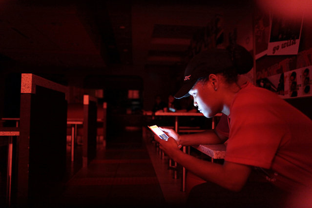 An employee at a fast-food restaurant in a shopping mall uses her mobile phone during a power outage that affected several areas in the country, in San Juan, Puerto Rico, September 21, 2016. (Photo by Alvin Baez/Reuters)