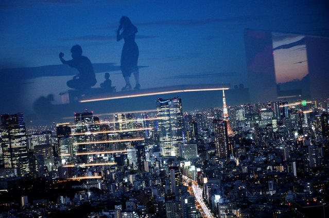 The Tokyo Tower (centre R) is illuminated amongst the city skyline as visitors are reflected in glass while visiting the Shibuya Sky observation deck in Tokyo on September 8, 2020. (Photo by Philip Fong/AFP Photo)