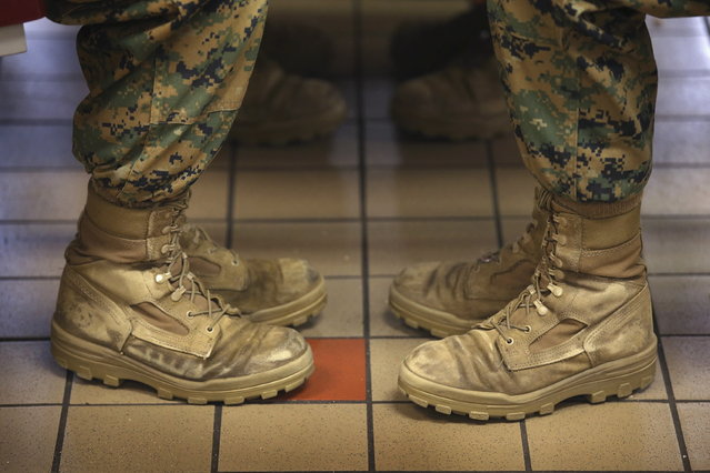 Female Marine recruits sit with their feet at a 45 degree angle, the same angle they are at while standing at the position of attention, while having lunch during boot camp on February 26, 2013 at MCRD Parris Island, South Carolina. Female enlisted Marines have gone through recruit training at the base since 1949. About 11 percent of female recruits who arrive at the boot camp fail to complete the training, which can be physically and mentally demanding. On January 24, 2013 Secretary of Defense Leon Panetta rescinded an order, which had been in place since 1994, that restricted women from being attached to ground combat units. (Photo by Scott Olson/AFP Photo)
