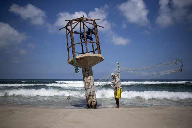A Palestinian fisherman cleans up his fishing net after the Israeli decision to close Gaza's fishing zone, on the beach in Gaza City, Tuesday, August 18, 2020. (Photo by Khalil Hamra/AP Photo)
