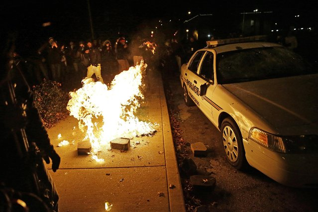 Protesters vandalize a police vehicle outside of the Ferguson city hall, Tuesday, November 25, 2014, in Ferguson, Mo. (Photo by David Goldman/AP Photo)