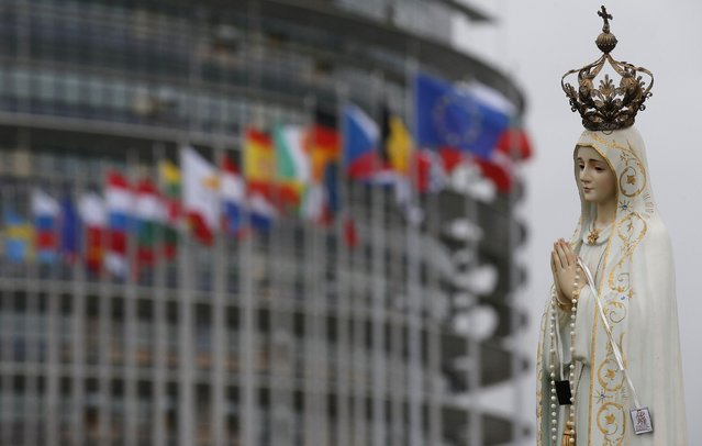 A figure of the Virgin Mary is displayed by faithful in front of the European Parliament building on the eve of the visit by Pope Francis to European institutions, in Strasbourg, November 24, 2014. Pope Francis will address the European Parliament and the Council of Europe on Tuesday in Strasbourg. (Photo by Christian Hartmann/Reuters)