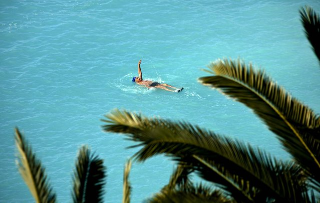 A man swims in the Mediterranean sea on a sunny day in Nice, France, on March 21, 2013. (Photo by Lionel Cironneau/Associated Press)