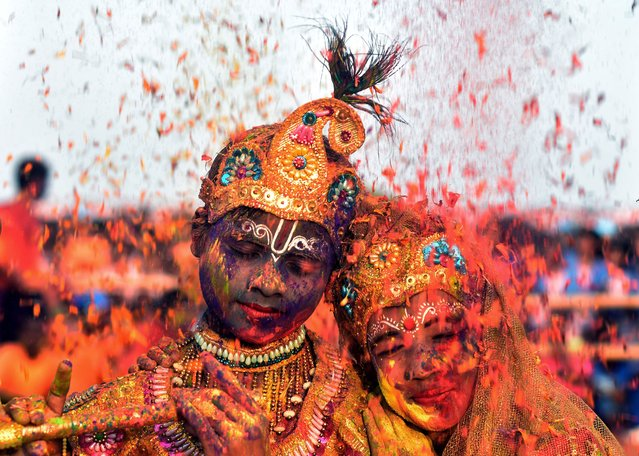 Tribal Indian students from the Kalinga Institute of Social Science (KISS), dressed as Lord Krishna and Radha, are smeared with with coloured powder and petals during Holi festival celebrations in Bhubaneswar on March 1, 2018. (Photo by Asit Kumar/AFP Photo)