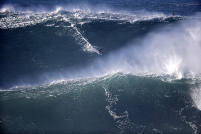 A surfer rides a big wave during a tow-in surfing session at the Praia do Norte or North beach, in Nazare, Portugal, Saturday, November 29, 2014. A tow-in is a surf technique in which the athlete is towed into a large wave by a partner driving a jet-ski with an attached tow-line. (Photo by Francisco Seco/AP Photo)