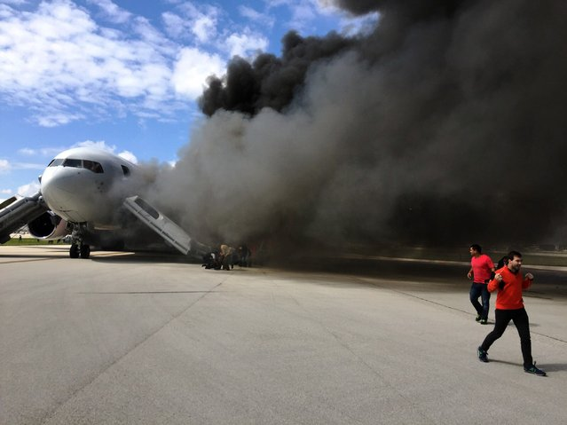 """Passengers are evacuate from a plane on fire at Fort Lauderdale airport, Florida on October 29, 2015. An airliner caught fire on a runway at Fort Lauderdale in Florida Thursday and several people were injured, authorities said. """"Airplane engine fire,"""" the Broward County Sheriff's Office said on Twitter, adding: """"several injuries"""". (Photo by Andres Gallego/AFP Photo)"""