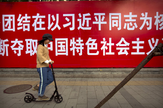 """In this October 12, 2017 photo, a woman rides a scooter past a banner which says """"To more closely unite around the party central committee with Comrade Xi Jinping as the core, continuously strive for achieving new victories of socialism with Chinese characteristics"""". in Beijing. At a twice-a-decade party congress in 2017, Xi sees his personal political philosophy  – """"Xi Jinping Thought on Socialism with Chinese characteristics for a New Era"""" – entered into the party constitution alongside those of his predecessors. Observers note that unlike his previous two predecessors, Xi is identified with his philosophy by name, placing him level with Mao and the revered reformist Deng Xiaoping. (Photo by Mark Schiefelbein/AP Photo)"""