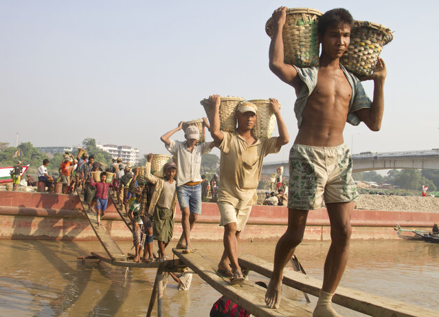 Myanmar's day laborers unload sands from a ship as they work at a construction site Wednesday, December 10, 2014, in Yangon, Myanmar. (Photo by Khin Maung Win/AP Photo)