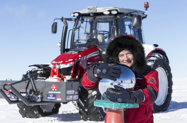 """A handout photo taken and released by Simon Foster Photography Ltd shows Dutch actress and adventurer Manon """"Tractor Girl"""" Ossevoort embracing a metallic sphere at the Ceremonial South Pole after arriving at the South Pole from Europe through Africa and across Antarctica by tractor on December 9, 2014. (Photo by Simon Foster/AFP Photo)"""