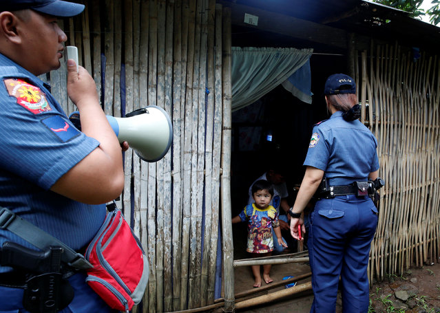 """A girl looks out from the entrance of a house as her grandfather prepares to go with the police to a police station as part of Operation """"Tokhang"""" (Knock and Persuade drug users to surrender) in Magalang, Pampanga in northern Philippines, October 8, 2016. (Photo by Erik De Castro/Reuters)"""