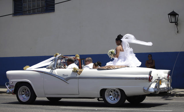 A bride rides a convertible car during a wedding celebration in Havana, April 17, 2013. (Photo by Desmond Boylan/Reuters)