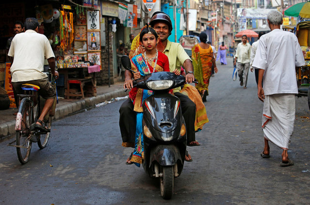 A man carries his daughter, dressed as Kumari, on a scooter, as they arrive to attend rituals to celebrate the Navratri Festival, on a road outside the Adyapeath Temple, on the outskirts of Kolkata, India on March 25, 2018. (Photo by Rupak De Chowdhuri/Reuters)