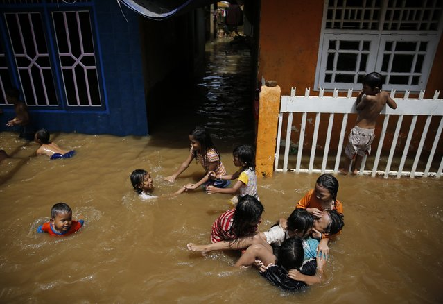 Children play at a flooded residential area at Kampung Melayu district in Jakarta, December 23, 2014. (Photo by Reuters/Beawiharta)