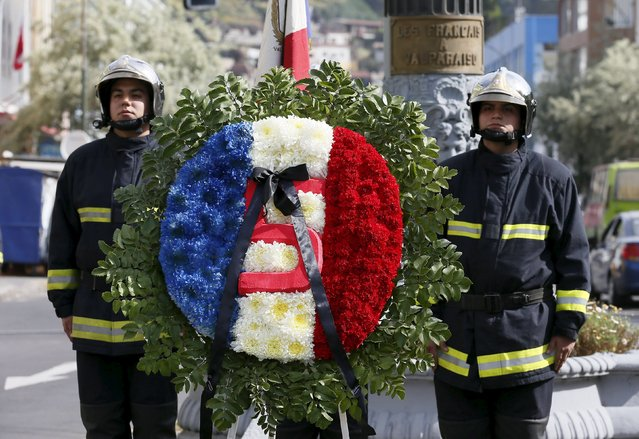 Firefighters of the Pompe France fire company lay tributes next to a wreath in memory of the victims of the Paris attacks, at a monument erected by the French government during colonial rule, in Valparaiso, Chile, November 14, 2015. (Photo by Rodrigo Garrido/Reuters)