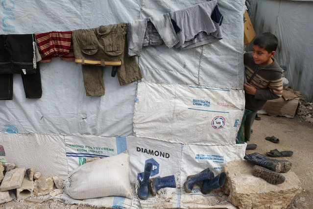 Syrian boy peeks outside of his tent at a refugee camp in Deir Zannoun village, Bekaa valley, Lebanon, Tuesday, January 6, 2015. (Photo by Hussein Malla/AP Photo)