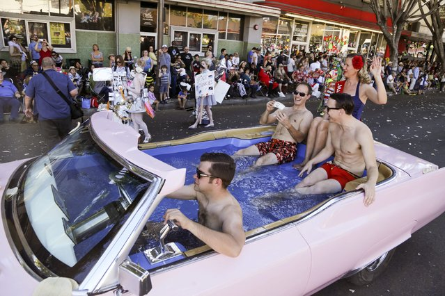 A pink cadillac converted into a swimming pool drives down Colorado Boulevard during the Doo Dah Parade in Pasadena, California, USA, 22 November 2015. The eccentric parade started as a grassroots event in 1978 with a focus on satire and homemade designs. Temperatures in the Southern California area were near record-breaking levels during the parade. (Photo by Eugene Garcia/EPA)