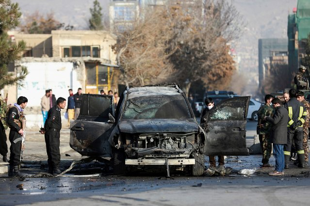 Afghan security personnel inspect a damaged vehicle after a bomb blast in Kabul, Afghanistan, Sunday, December 13, 2020. A sticky bomb attached to an armored vehicle in northern Kabul killed a few, and wounded at least a few others, according to Ferdaws Faramarz, a spokesman for the Kabul police chief. No further details were immediately available. (Photo by Rahmat Gul/AP Photo)
