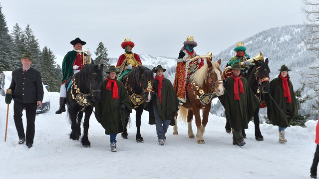 Locals dressed as traditional carol singers ride on horses on Monday, January 5, 2015 in Dienten, Austrian province of Salzburg. Traditionally carol singers walk from house to house around epiphany to collect money for poor children in other countries. (Photo by Kerstin Joensson/AP Photo)