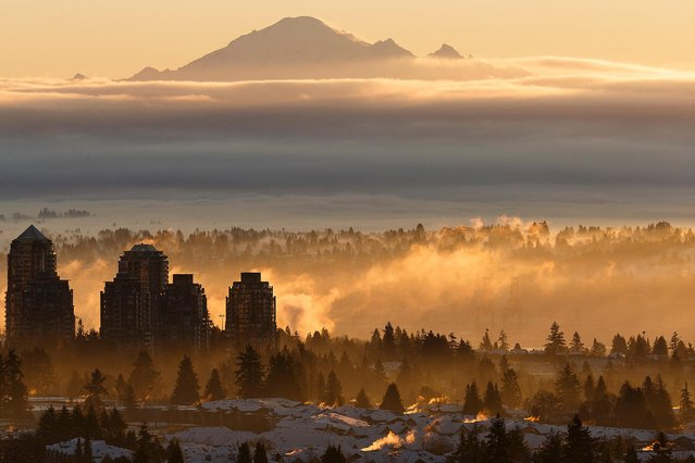 A temperature inversion is seen over Metro Vancouver against Mount Baker at sunrise on December 22, 2020 in Burnaby, British Columbia, Canada. The Provincial Health Officer (PHO) has ordered that events and gatherings be suspended in order to reduce the transmission of COVID-19 through social contact and travel. The order lasts from November 19, 2020 at midnight to January 8, 2021 at midnight. (Photo by Andrew Chin/Getty Images)