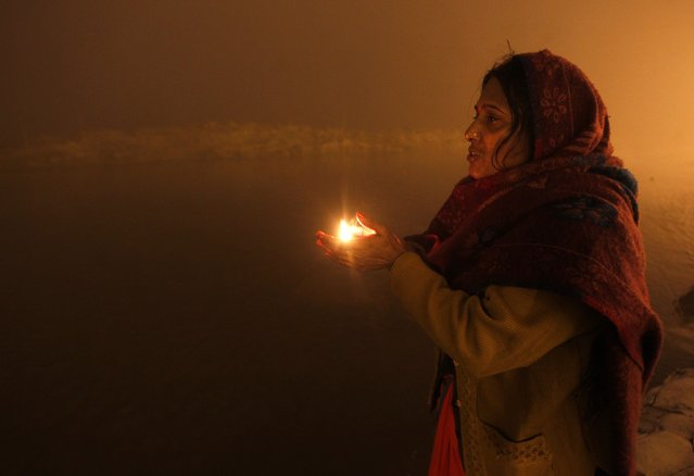A Hindu devotee holds an earthen oil lamp as she prays after taking a holy dip at Sangam during the Magh Mela festival, on an early winter morning in the northern Indian city of Allahabad January 15, 2015. The festival is an annual religious event held during the Hindu month of Magh, when thousands of devotees take a holy dip in the waters of Sangam, the confluence of the Ganges, Yamuna and Saraswati rivers. (Photo by Jitendra Prakash/Reuters)
