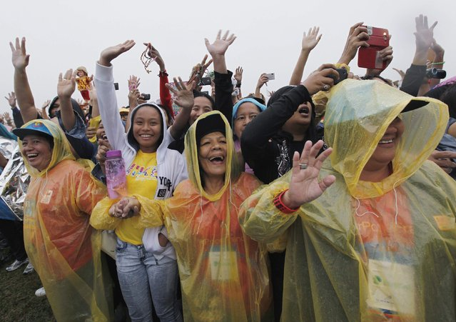 Well-wishers wait for the arrival of Pope Francis prior to an open-air Mass in Manila January 18, 2015. (Photo by Paul Barker/Reuters)