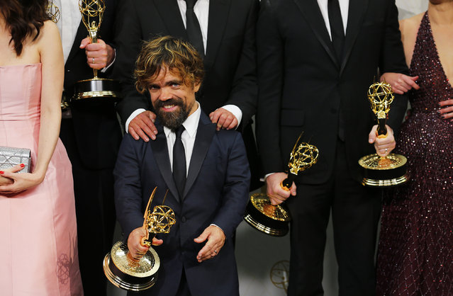 """Peter Dinklage and the cast of HBO's """"Game of Thrones"""" pose backstage with their Outstanding Drama Series award during the 67th Primetime Emmy Awards in Los Angeles, September 20, 2015. (Photo by Mike Blake/Reuters)"""