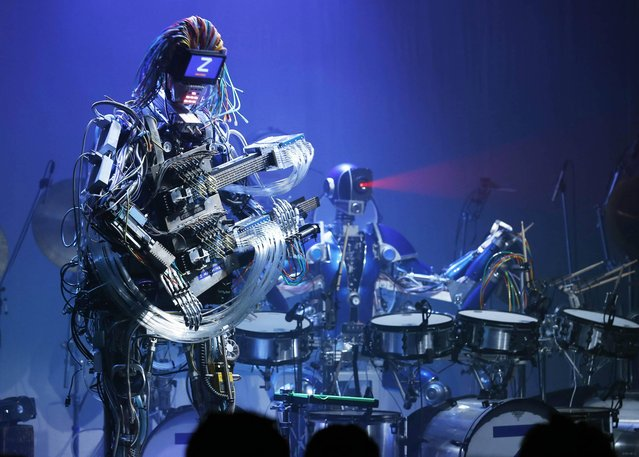 Robot music band Z-Machines members, guitarist robot Mach, left, and drummer robot Ashura, perform at their debut live event in Tokyo Monday, June 24, 2013. Supervised by Japanese artists and creators, Z-Machines has been developed to realize the cutting edge party scene by featuring the guitarist robot with 78 fingers and 12 picks, the drummer robot with 21 sticks and a keyboard player robot that can flash multi-layered beams from its eyes, enabling transcendental music performance. (Photo by Koji Sasahara/AP Photo)