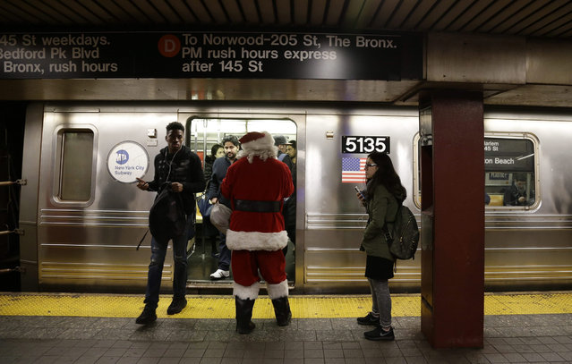 A person dressed as Santa Claus waits to board a train at 34th Street subway station in New York, New York, USA, 09 December 2015. (Photo by Jason Szenes/EPA)