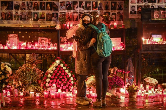 "A young girl wearing wings is embraced by another next to candles lit in the memory of the victims of ""Colectiv"" nightclub fire in Bucharest, Romania on October 30, 2020. The deadly nightclub fire killed three of her friends and left her with severe burns. Hundreds people on the night of October 30, 2015 was trapped inside ""Colectiv"", a former-factory-turned-club in the center of Bucharest, when a fire sparked by pyrotechnics engulfed the place during a concert held by the local rock band ""Goodbye to Gravity"". A total of 64 people died and hundreds were injured. The blaze stunned Romania, triggering a wave of anti-corruption protests and a nationwide debate about administrative incompetenc. (Photo by Daniel Mihailescu/AFP Photo)"