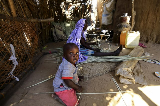 An internally displaced child plays while the mother weaves a traditional handcraft inside their shelter in Kalma camp in Nyala, South Darfur, Sudan, November 22, 2015. (Photo by Mohamed Nureldin Abdallah/Reuters)
