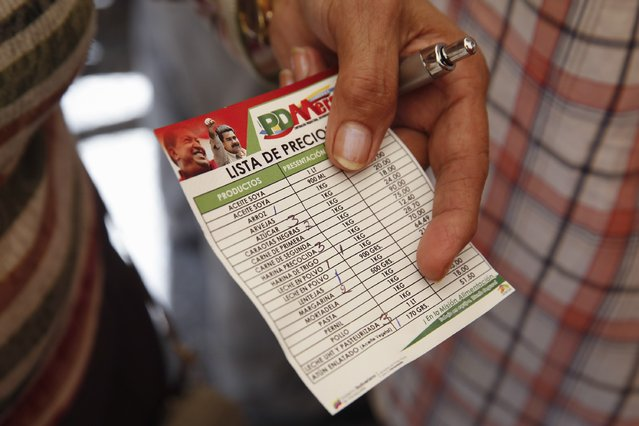 A woman shows a purchase control and price list card in a Mega-Mercal, a subsidized state-run street market, in Caracas January 24, 2015. (Photo by Carlos Garcia Rawlins/Reuters)