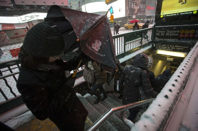 A woman descends into the subway as snow falls in Times Square in New York, January 26, 2015. The National Weather Service (NWS) issued a blizzard warning for New York City and surrounding areas on Monday, and warned of two days of winter storms across the East Coast, from Pennsylvania to Maine. (Photo by Mike Segar/Reuters)