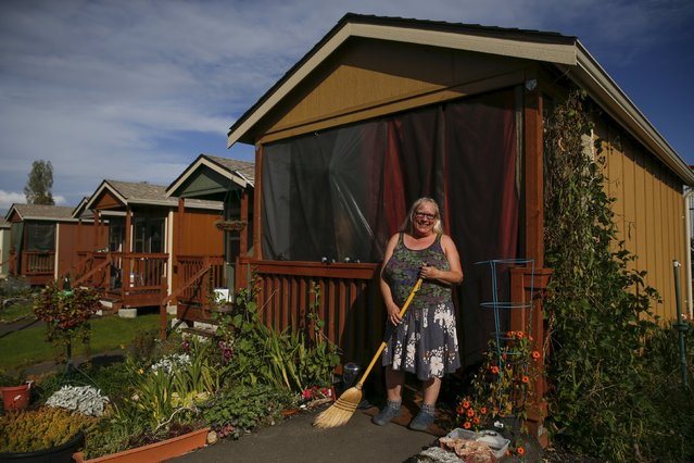 "Sharon Wilson, 59, poses outside her cottage in Olympia, Washington October 11, 2015. Quixote Village is made up of 30 cottages, a community building with a kitchen, showers and laundry facilities and a vegetable garden. ""Moving inside was a culture shock for a lot of the hardcore campers. I will never forget the first morning we woke up here. One of the residents went outside looking for the outhouse, not realising he had a bathroom"", said Wilson. (Photo by Shannon Stapleton/Reuters)"