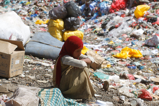 A girl sits on a pile of rubbish at landfill site on the outskirts of Sanaa, Yemen November 16, 2016. (Photo by Mohamed al-Sayaghi/Reuters)