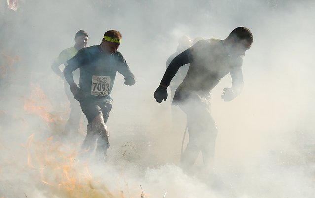 Competitors run through smoke and fire during the Tough Guy event in Perton, central England, February 1, 2015. (Photo by Phil Noble/Reuters)